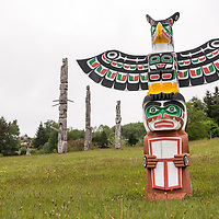 Totem poles at the 'Namgis burial grounds and cemetery in Alert Bay, Cormorant Island, British Columbia, Canada. Pole is Thunderbird, Man holding Copper carved by Bruce Alfred.