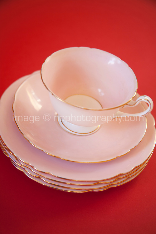 Pink china tea cup and saucer and plates with gold trim on a red background