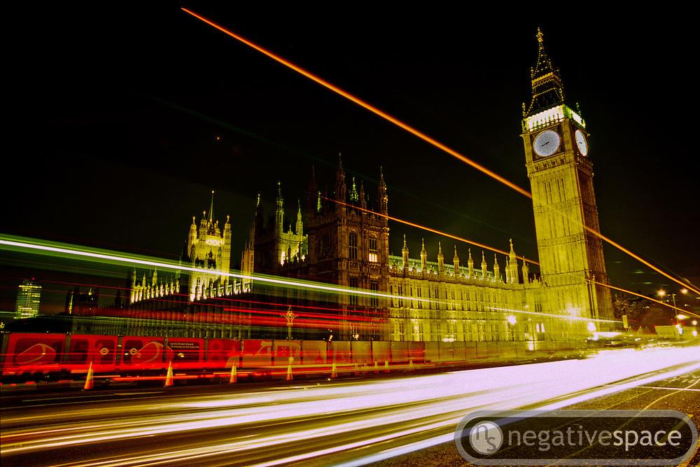 Cars at night blazing past Big Ben and Parliament, London, England