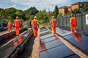 THe installers walk through the array of solar panels next to the line near Aldershot Railway Station.  This innovative project is the first in the UK to power the railway with electricity generated from solar power and, if successful, could see many Network Rail sites across the country adapting this sustainable energy approach. Riding Sunbeams is a social enterprise, run by 10:10 Climate Action. Built with Community Energy South and partnered with Network Rail and The Department for Transport and by InnovateUK.  Aldershot, Hampshire, United Kingdom. Riding Sunbeams is a world leading project to connect solar panels directly into electrified rail routes to power the trains. Direct supply of solar power to rail traction systems has never been done. But it has huge potential - from metros, trams and railways in the UK and around the world.<br /> (photo by Andy Aitchison / 1010 Climate Action)