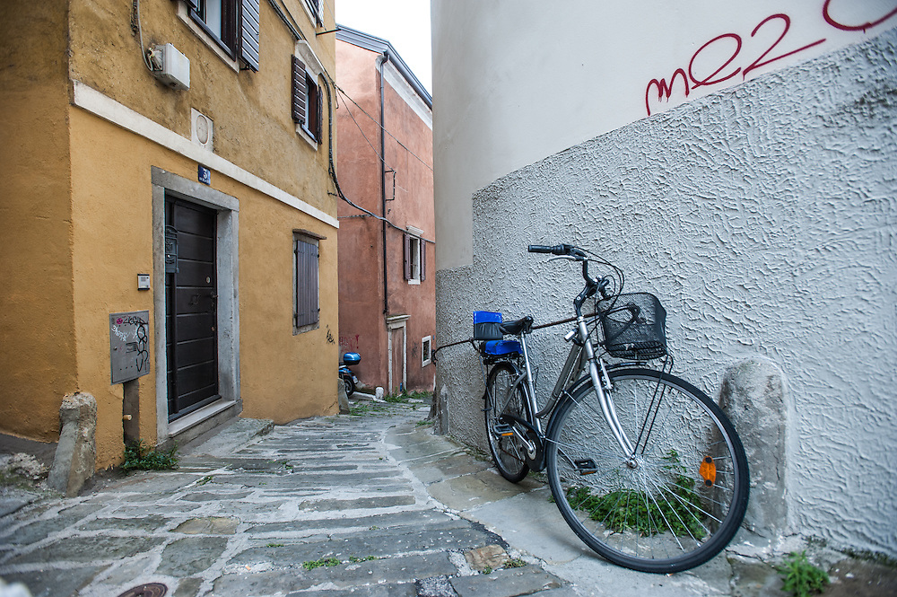 A bicycle is parked on a steep pedestrian road of the old city (Città Vecia) in Trieste, Italy.
