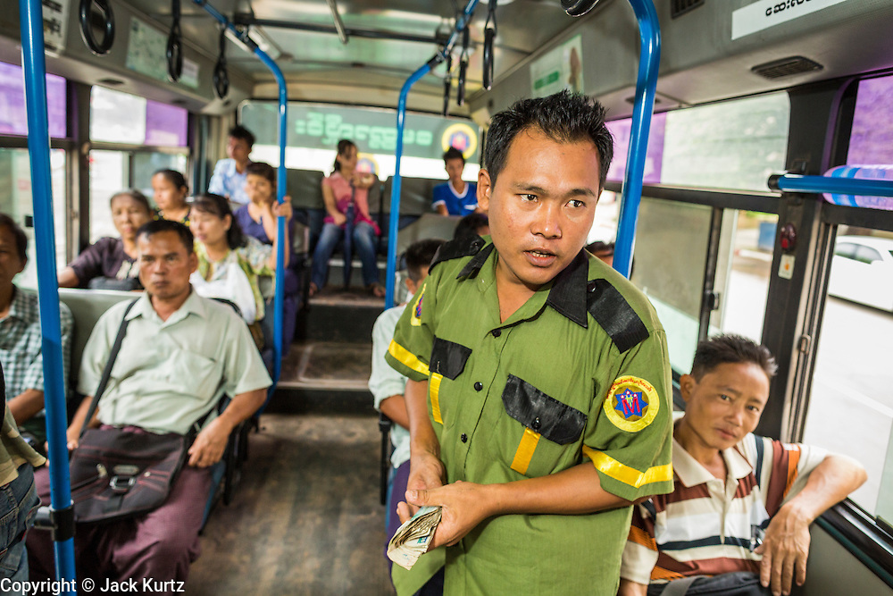 19 JUNE 2013 - YANGON, MYANMAR: A conductor collects fares on a Yangon bus. Yangon buses are generally overcrowded and in poor repair but as the economy improves newer, but still used, Japanese and Korean buses are being imported. Hundreds of bus routes criss-cross Yangon, providing the cheapest way of getting around the city. Most fares are less than the equivalent of .20¢ US.   PHOTO BY JACK KURTZ