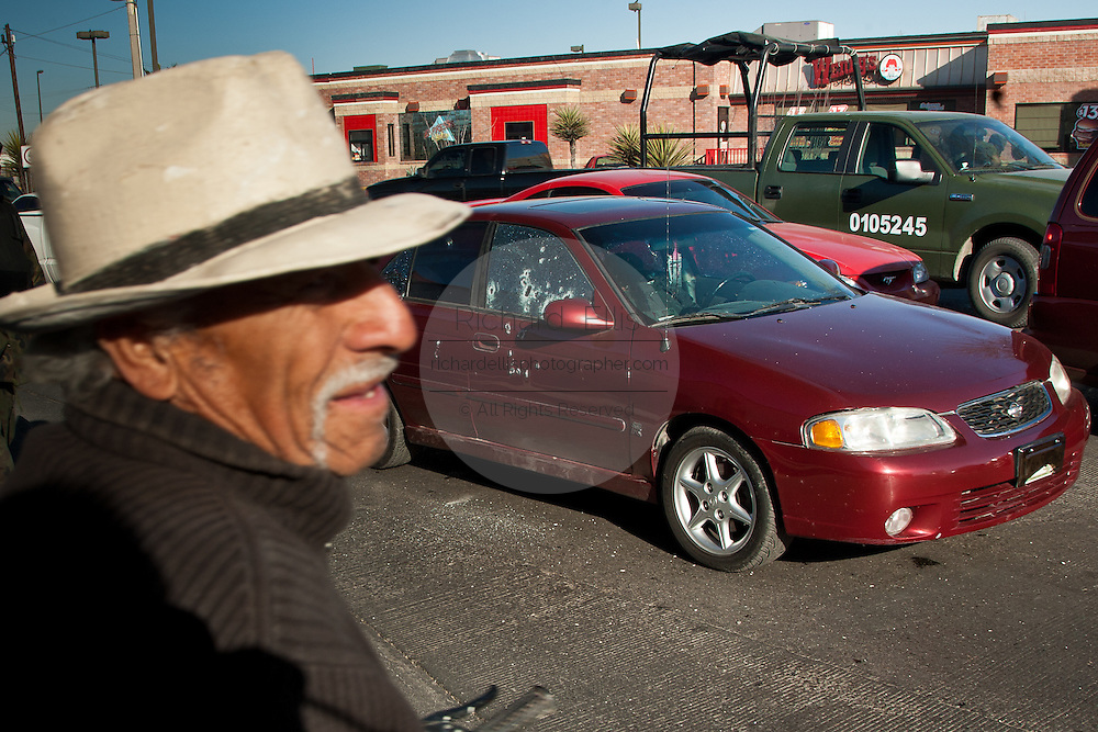 A bewildered pedestrian watches the  Mexican Army respond to a assignation along a main road in Juarez, Mexico January 16, 2009 moments after armed gunman shot dead a former police officer during morning rush hour as the dead man lies behind the wheel in the red car. The shooting, believed linked to the ongoing drug war which has already claimed more than 40 people since the start of the year. More than 1600 people were killed in Juarez in 2008, making Juarez the most violent city in Mexico.    (Photo by Richard Ellis)