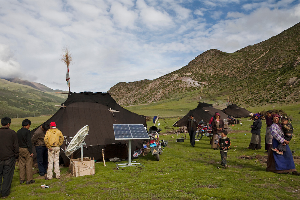 A group of Tibetan nomads show off their satellite dish outside the handmade yak-wool tents where they make their home in spring and summer in the Tibetan Plateau. (From the book What I Eat: Around the World in 80 Diets.)