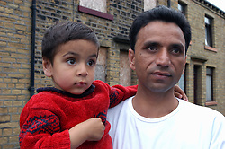 Father & son living in deprived area of Halifax; Yorkshire, UK, Boarded up houses in background