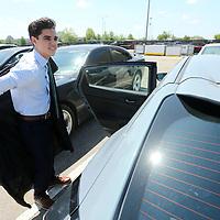Jeb Thomas, a Mooreville graduating senior, gets his robe on by his car in the parking lot at the BancorpSouth Arena for the Mooreville High School graduation Saturday.