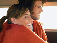 Couple wrapped in blanket in front seat of van profile head and shoulders
