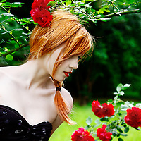 Young female redhead looking down at roses