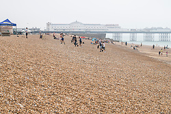 © Licensed to London News Pictures. 26/06/2020. Brighton, UK. Only a handful of visitors brave the beach on Friday morning as colder weather and fog is hitting the Brighton and Hove coast. Photo credit: Hugo Michiels/LNP
