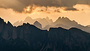 Sunset light turns orange over sharp peaks of the Dolomites, or Dolomiti, a part of the Southern Limestone Alps, in northern Italy, Europe. The view looks westwards from a trail west of Gasthaus Passo di Giau. The Dolomites are honored as a natural World Heritage Site (2009) by UNESCO.