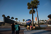 CAPE CANAVERAL, FL | March 1, 2016<br /> Tourists pause at the entrance way to the Kennedy Space Center Visitor Complex, while a model of the Space Shuttle Atlantis, with its dual rocket boosters and orange external tank, sits in the distance.<br /> <br /> (Melissa Lyttle for The New York Times)