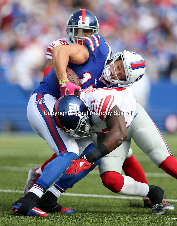 Buffalo Bills wide receiver Chris Hogan (15) gets hit hard by New York Giants free safety Landon Collins (21) on a second quarter pass reception as New York Giants cornerback Trumaine McBride (38) closes in from behind during the 2015 NFL week 4 regular season football game against the New York Giants on Sunday, Oct. 4, 2015 in Orchard Park, N.Y. The Giants won the game 24-10. (©Paul Anthony Spinelli)