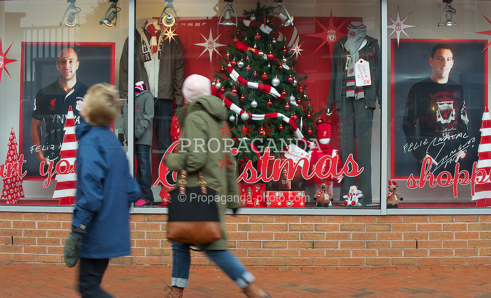 LIVERPOOL, ENGLAND - Saturday, December 10, 2011: Liverpool fans walk past the Christmas window display of the club shop at Anfield before Liverpool play Queens Park Rangers. (Pic by David Rawcliffe/Propaganda)