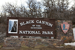 Welcome sign at the southern entrance to Black Canyon of the Gunnison National Park is a United States National Park located near Montrose, Colorado in the western part of the state. The park is managed by the National Park Service. There are two entrances to the park; the more-developed south rim entrance is located 15 miles (24 km) east of Montrose, while the north rim entrance is located 11 miles (18 km) south of Crawford and is closed in the winter. The park contains 12 miles of the 48 mile long canyon of the Gunnison river. The park contains the deepest and most dramatic section of the canyon, one of the deepest mountain descents in North America.  The canyon continues upstream into the Curecanti National Recreation Area and downstream into the Gunnison Gorge National Conservation Area.