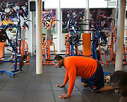 Jay Bromley, a defensive tackle for the Syracuse University football team, does a hip exercise during a workout in Syracuse, New York on Friday, May 2, 2014. Bromley, who attended Flushing High School, is projected as a late-round NFL draft pick.