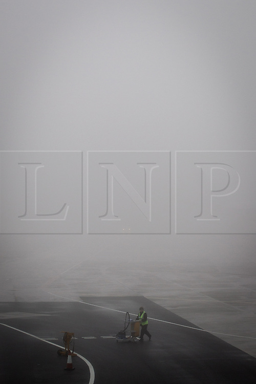 © Licensed to London News Pictures . 09/01/2013 . Manchester , UK . An airport worker crosses the tarmac as the airfield behind him is clouded in thick fog . Thick fog is causing flight delays and cancellations in the North of England today (9th January 2013) . Photo credit : Joel Goodman/LNP