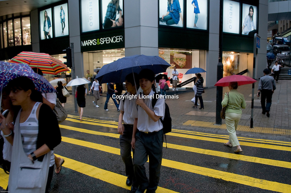Two school kids in uniform cross Queen's road in Central in front of Marks & Spencer showing the English heritage of Hong Kong. 2009.<br /> <br /> Deux ecoliers en uniformes traversent Queen's road a Central devant le magasin Marks&Spencer heritage direct des anglais. Hong Kong 2009.