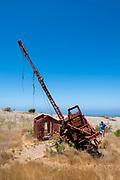 A young man examines an abandoned oil drilling rig along Smugglers Road atop Santa Cruz Island, Channel Islands National Park, California, USA.