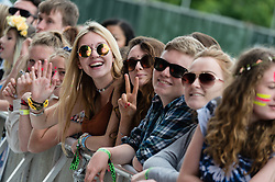 © Licensed to London News Pictures. 13/06/2015. Isle of Wight, UK.  Girls smile in the afternoon sun as they wait to watch Ella Eyre perform at Isle of Wight Festival 2015 on Saturday Day 3.  Yesterday suffered torrential rain all afternoon and evening, after a first day of warm sun.  This years festival include headline artists the Prodigy, Blur and Fleetwood Mac.  Photo credit : Richard Isaac/LNP