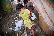 A young girl is carrying a child across a muddy path in the impoverished Oriya Basti colony in Bhopal, Madhya Pradesh, India, near the abandoned Union Carbide (now DOW Chemical) industrial complex.