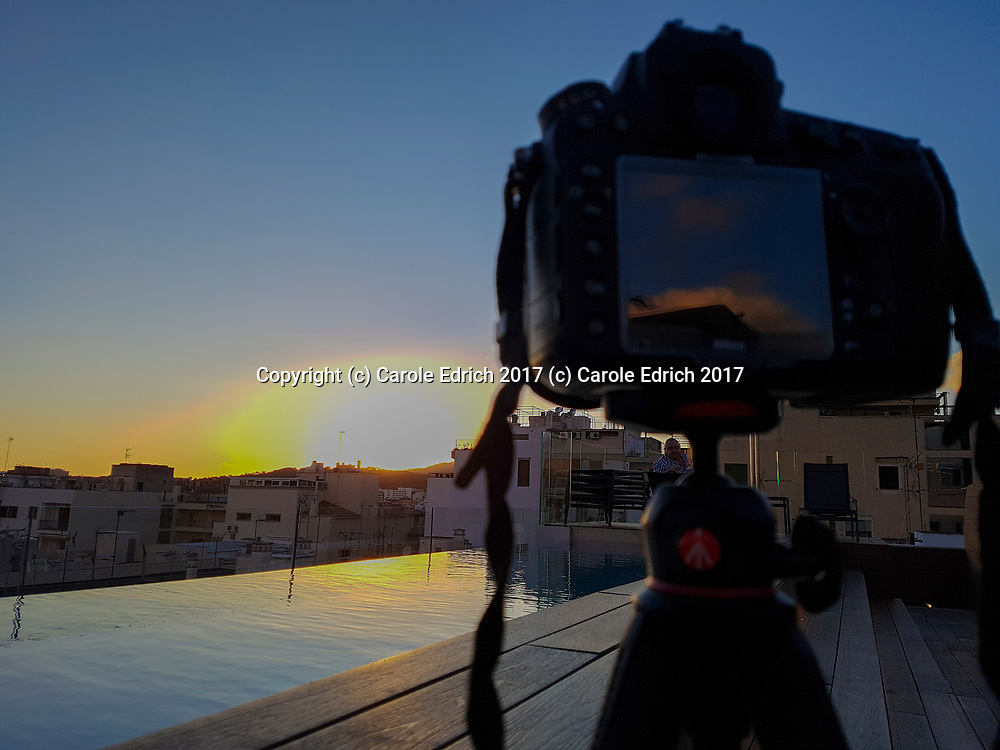 Nikon camera on tripod photographing sunset which is reflected in Nakar Hotel rooftop pool. Camera itself reflects salmon pink clouds and roof. (c) Carole Edrich 2017