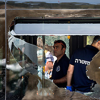An Israeli forensic police officer inspects the scene of a shooting attack in Jerusalem, Tuesday, Oct. 13, 2015. A pair of Palestinian men boarded a bus in Jerusalem and began shooting and stabbing passengers, while another terrorist rammed a car into a bus station before stabbing bystanders, in near-simultaneous attacks. <br />