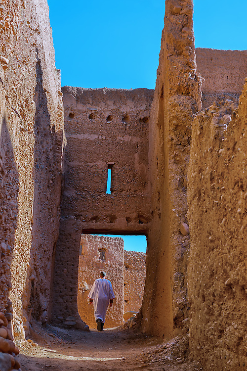 Traditional dressed man walks inside a kasbah, Tamnougalte, Morocco.