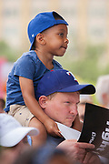 A young attendee sits high on a pair of shoulders while listening to speakers during the Familes Belong Together rally in front of City Hall in Dallas.