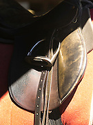 A shadow slants across an English/Eastern riding saddle with the stirrups up.