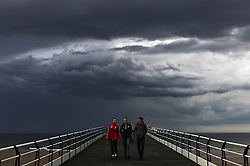 © Licensed to London News Pictures. <br /> 08/06/2014. <br /> <br /> Saltburn, United Kingdom<br /> <br /> Three friends walk back along the pier as dark and brooding thunder clouds form behind them over the sea in Saltburn, Cleveland.<br /> <br /> Photo credit : Ian Forsyth/LNP
