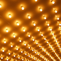 Picture of theater marquee lights in rows at night on a movie theatre exterior. This style of lighting is commonly known as Broadway lights, casino lights or theater lights. Image is high resolution and is available as a stock photo, poster or print.