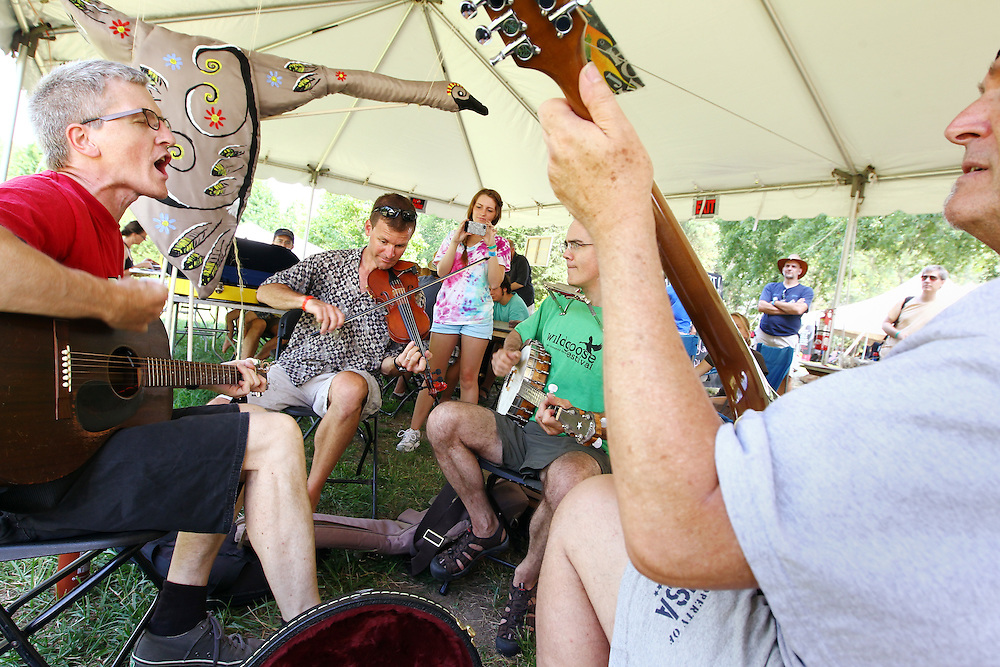 An impromptu musical jam springs up in the art tent at the Wild Goose Festival at Shakori Hills in North Carolina June 24, 2011.  (Photo by Courtney Perry)