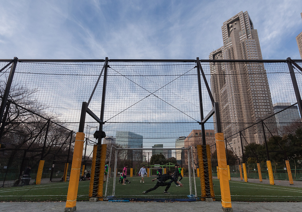 People play five-a-side football in a footsal court under the Tokyo Metropolitan Government Towers in Shinjuku, Tokyo, Japan. Thursday February 15th 2018