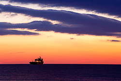 A ship under clouds over the Atlantic Ocean before sunrise, Rye, New Hampshire.