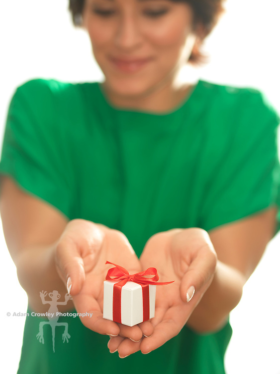 Hispanic woman (20-30) hollds in her hands a small white gift box wrapped in red ribbon.