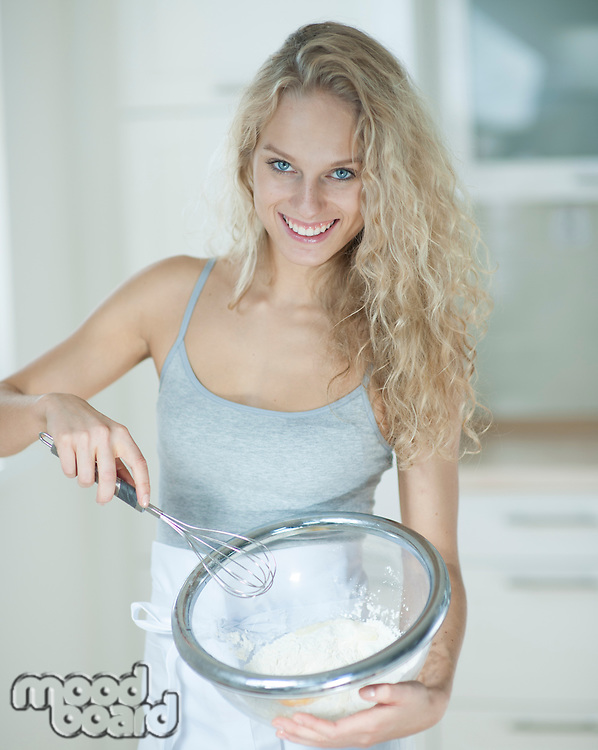 Portrait of woman mixing cookie batter in kitchen