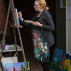 A woman painting on the street during the opening day of the Worthington's Farmer's Market May 3, 2014. (Christina Paolucci, photographer).