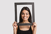 Portrait of young woman smiling through frame over white background