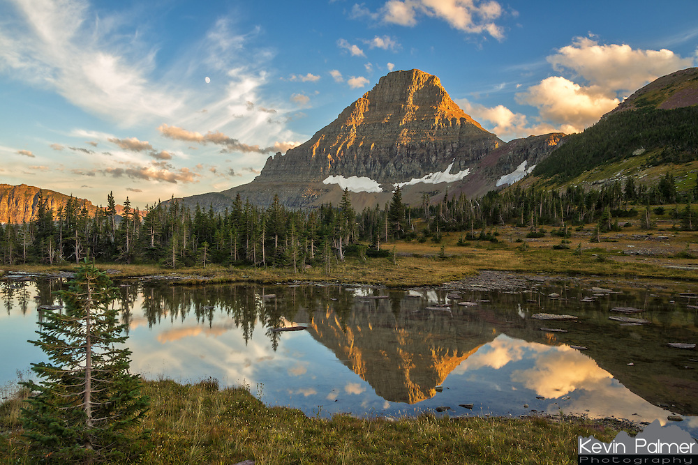 Reynolds Mountain glows from the last light of the day in Glacier National Park, Montana. This small pond can be found above Logan Pass, along the Hidden Lake trail. There was not much snow remaining on the peaks after a long hot summer.