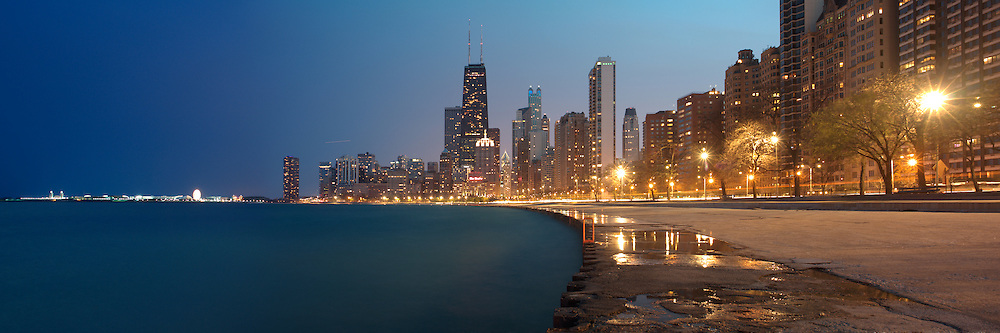 The John Hancock Center and Navy Pier are seen along Lakeshore Drive at dusk.