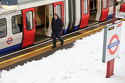 © Licensed to London News Pictures. 11/12/2017. Amersham, UK. A man walks past a platform covered in snow at at Amersham Underground Station in Buckinghamshire. Transport is being heavily affected across parts of the islands and southern England with British Airways cancelling 30 flights before 10am this morning. Photo credit: Tom Nicholson/LNP