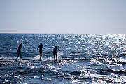 Young teens playing in the sea at dusk. Back lit by the setting sun