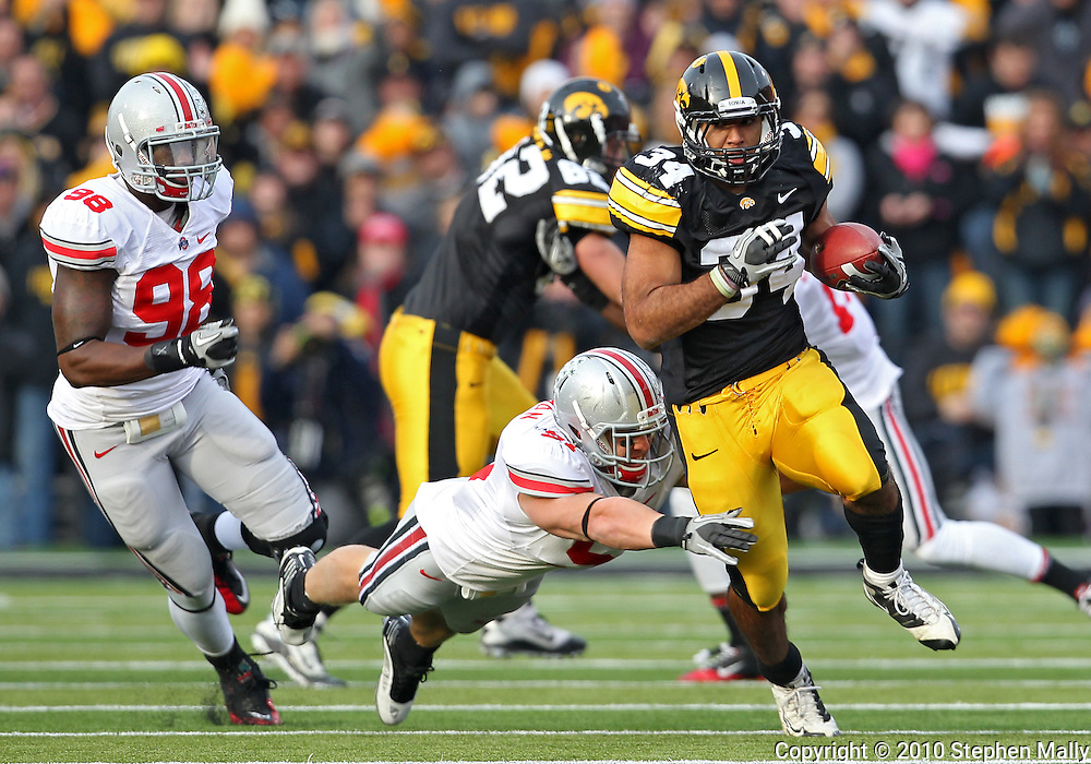 November 20 2010: Iowa Hawkeyes running back Marcus Coker (34) pulls away from a diving Ohio State Buckeyes linebacker Ross Homan (51) during the first quarter of the NCAA football game between the Ohio State Buckeyes and the Iowa Hawkeyes at Kinnick Stadium in Iowa City, Iowa on Saturday November 20, 2010. Ohio State defeated Iowa 20-17.