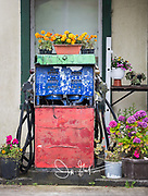 An old gas pump surrounded by colorful flowers.