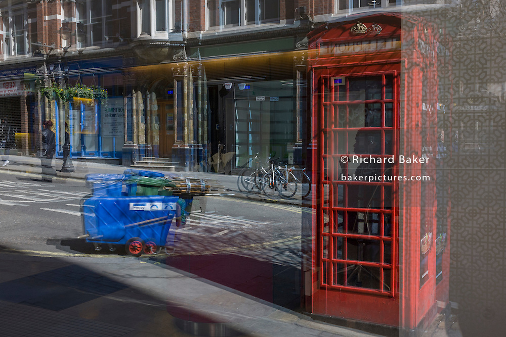 Seen through an office foyer window, including a receptionist appearing in red phone box kiosk.