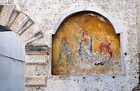 Alessano (Lecce) - Icona posizionata accanto ad un portone, Via ... L'icona rappresenta Gesù Cristo al centro e reca nella mano destra la rappresentazione del mondo; a sinistra del Cristo c'è un santo che ad un primo esame sembrerebbe essere San Lorenzo: nella mano destra ha una palma; a sinistra del Cristo la Madonna schiaccia la testa del serpente, rappresentazione del peccato originale.