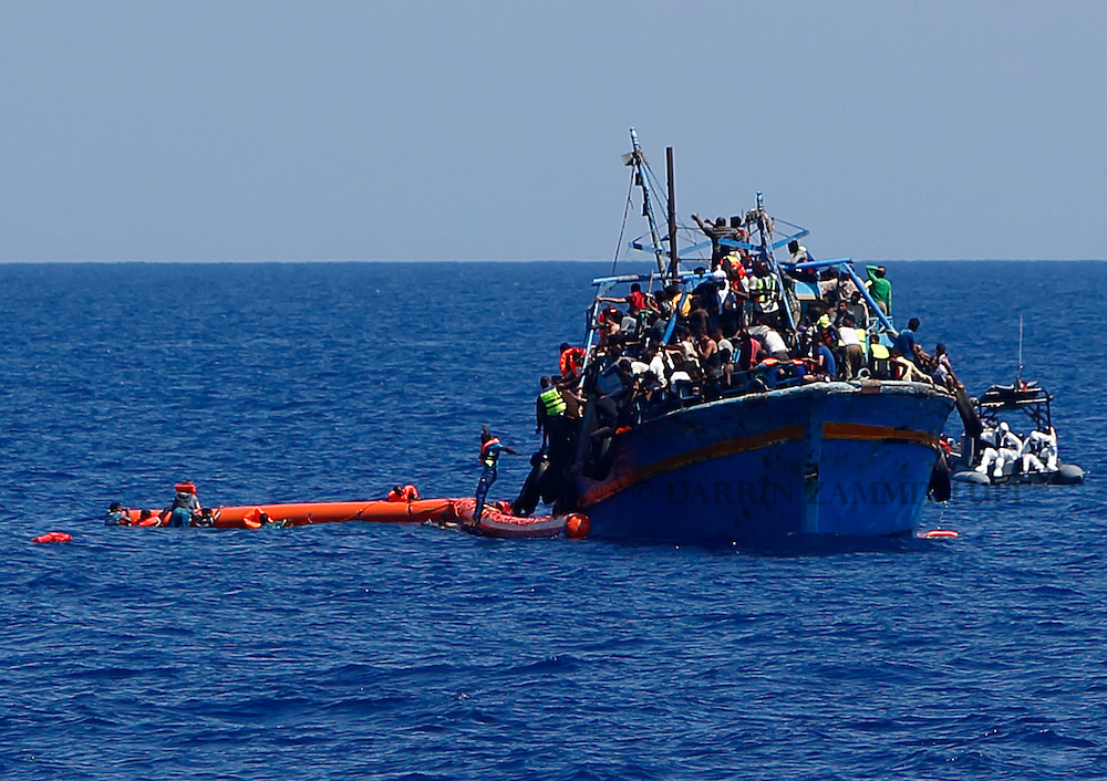 A migrant jumps into the water from an overloaded wooden boat as others hang onto flotation tubes in the sea during a rescue operation 10.5 miles (16 kilometres) off the coast of Libya August 6, 2015.  An estimated 600 migrants on the boat were rescued by the international non-governmental organisations Medecins san Frontiere (MSF) and the Migrant Offshore Aid Station (MOAS) without loss of life on Thursday afternoon, a day after more than 200 migrants are feared to have drowned in the latest Mediterranean boat tragedy after rescuers saved over 370 people from a capsized boat thought to be carrying 600.  Picture taken August 6, 2015.<br /> REUTERS/Darrin Zammit Lupi <br /> MALTA OUT. NO COMMERCIAL OR EDITORIAL SALES IN MALTA