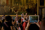 Tourists admire the Coronation of Napoleon in Coronation room of the King's apartments in the Palace of Versaille, near Paris. The painting (Le Sacre de Napoléon) is a work of almost 10 x 6 metres completed in 1807 by Jacques-Louis David, the official painter of Napoleon. The crowning and the coronation took place at Notre-Dame de Paris, a way for Napoleon to make it clear that he was a son of the Revolution.