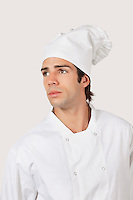 Pensive young man in chef's uniform looking away against gray background