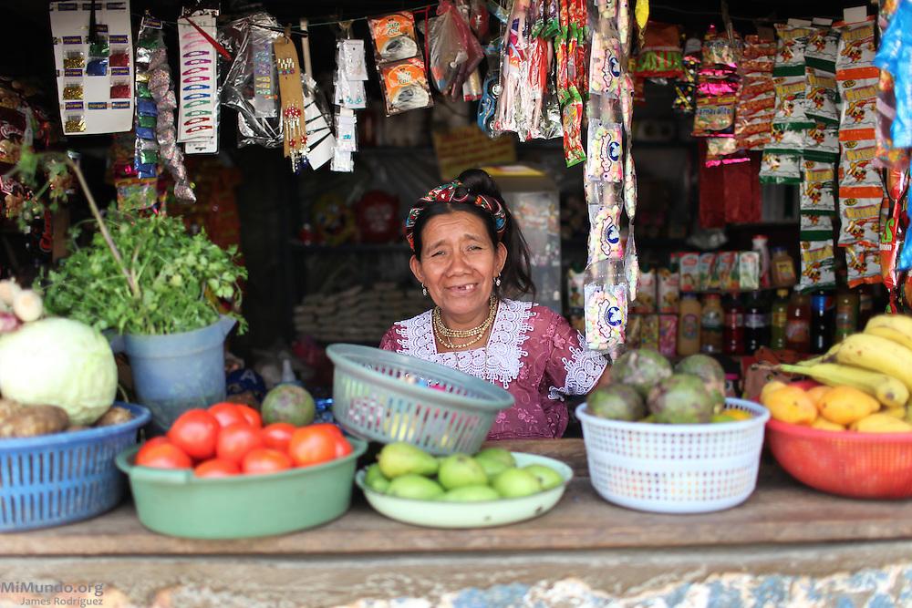 A Jakaltek mayan woman smiles from behind the counter of her local community store. Santiago Petatan, Concepción Huista, Huehuetenango, Guatemala. February 4, 2013.